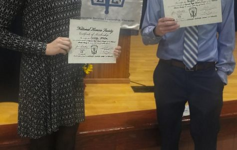 Students Caleigh Jensen and Ryan Hughes receive their National Honor Society members certificates