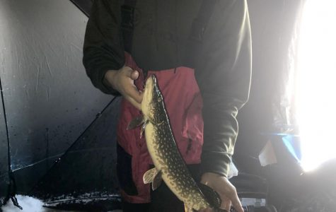 Senior Michael Strong holds a Northern he caught on Jan 1 on Spooner Lake.