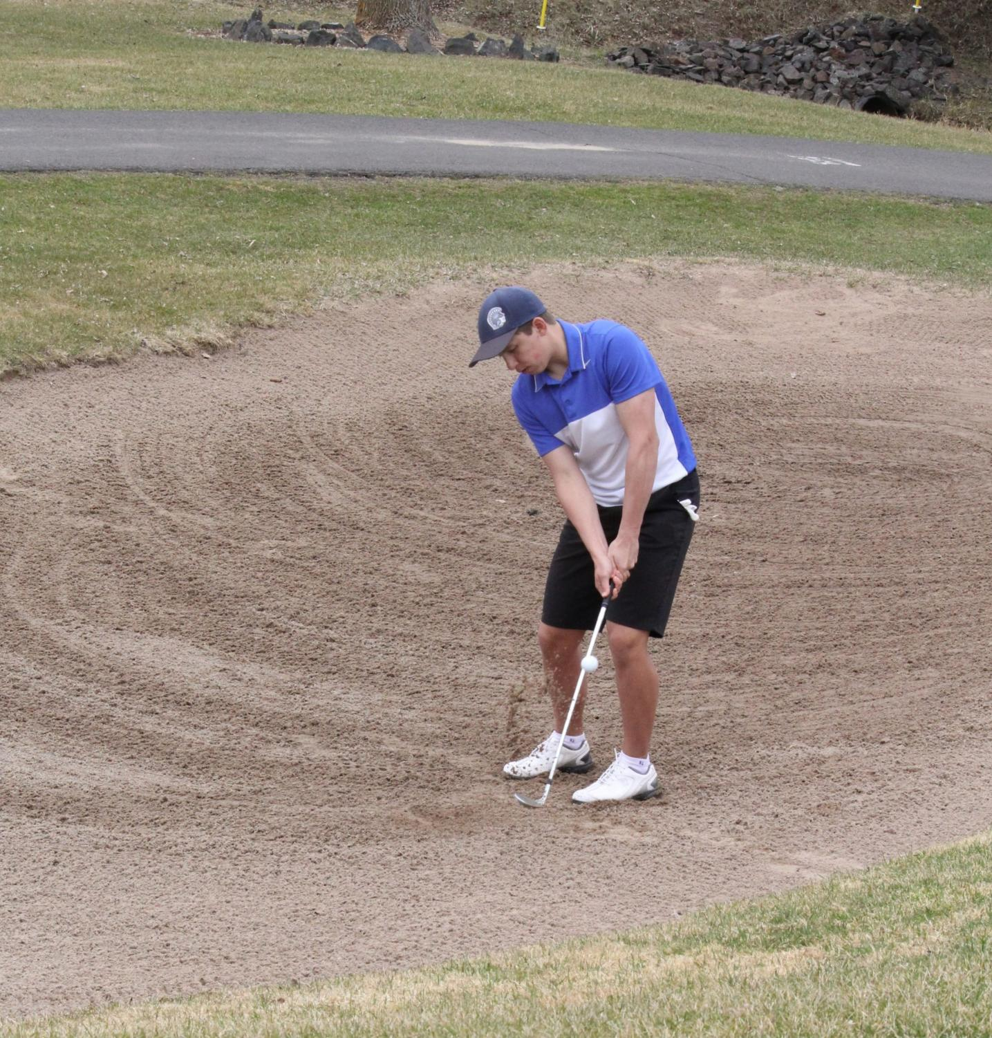 : Sophomore TJ Sitek chips out of the sand on the 10th hole of the south course at Nemadji Golf Course on Wed. May 2.