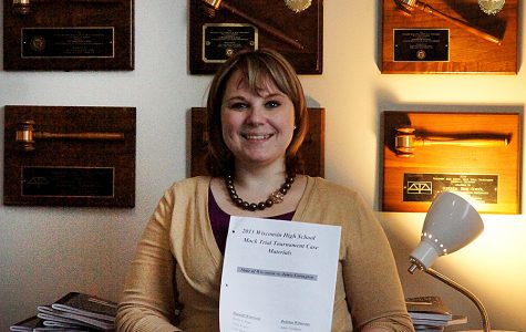 Mock trial coach Danielle Gondik-Anderson poses with the older case and mock trial awards.