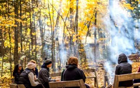 Students warm up around a fire at the school forest on Oct. 16