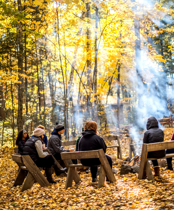 Students+warm+up+around+a+fire+at+the+school+forest+on+Oct.+16%0A