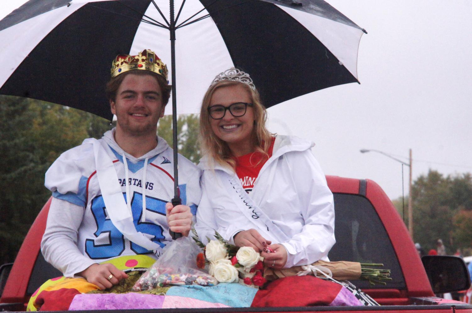 Homecoming queen and king Mady Stariha and Lars Root pose for a photo during the Homecoming parade while throwing candy to the spectators on Oct 5.