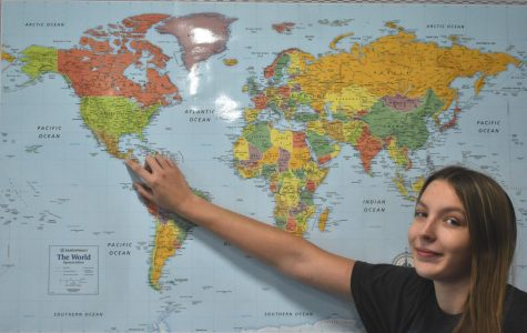 Senior Shanna Smith points at country Guatemala on a world map, displaying what country she is the representative for the Harvard Model United Nations Conference this January.