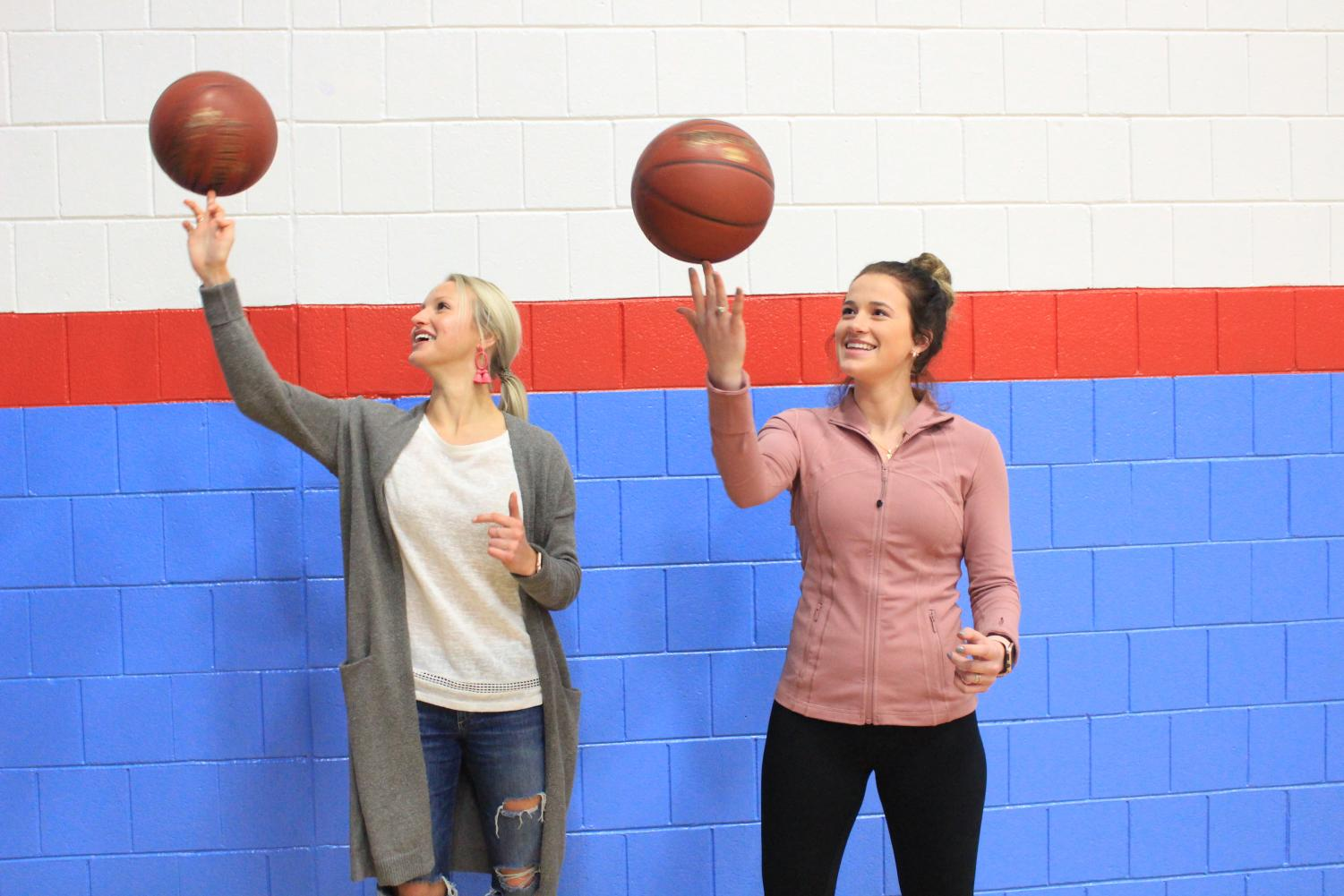 Seniors Chloe Kintop (left) and Maddy Myer twirl their basketballs in the gymnasium on Nov 16. Myer and Kintop are both part of the basketball team.