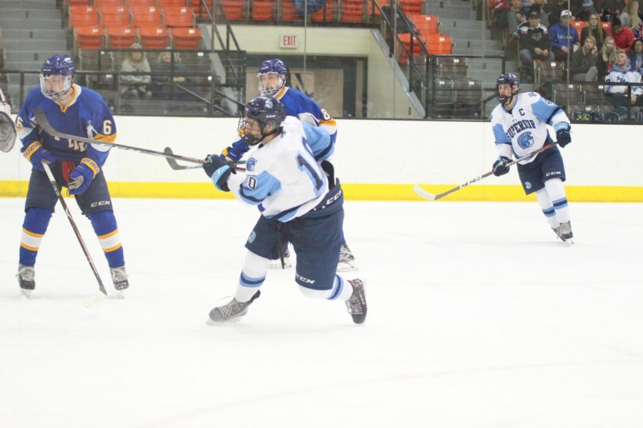 Senior Grant Sorensen (10) scores a goal against Rice Lake at 7:48 in the second period at Wessman Arena Friday night. Senior Cayden Laurvick (4, right) assisted along with junior Alex Hanson (not pictured). The Spartans won 9-1.
