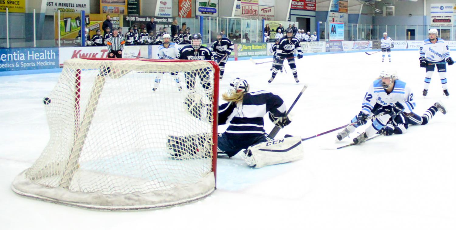 Sophomore Brooklyn Burger (12) slips the puck past Hudson goaltender Alayna Kushiner (1) at Superior Ice Arena Dec. 8.
