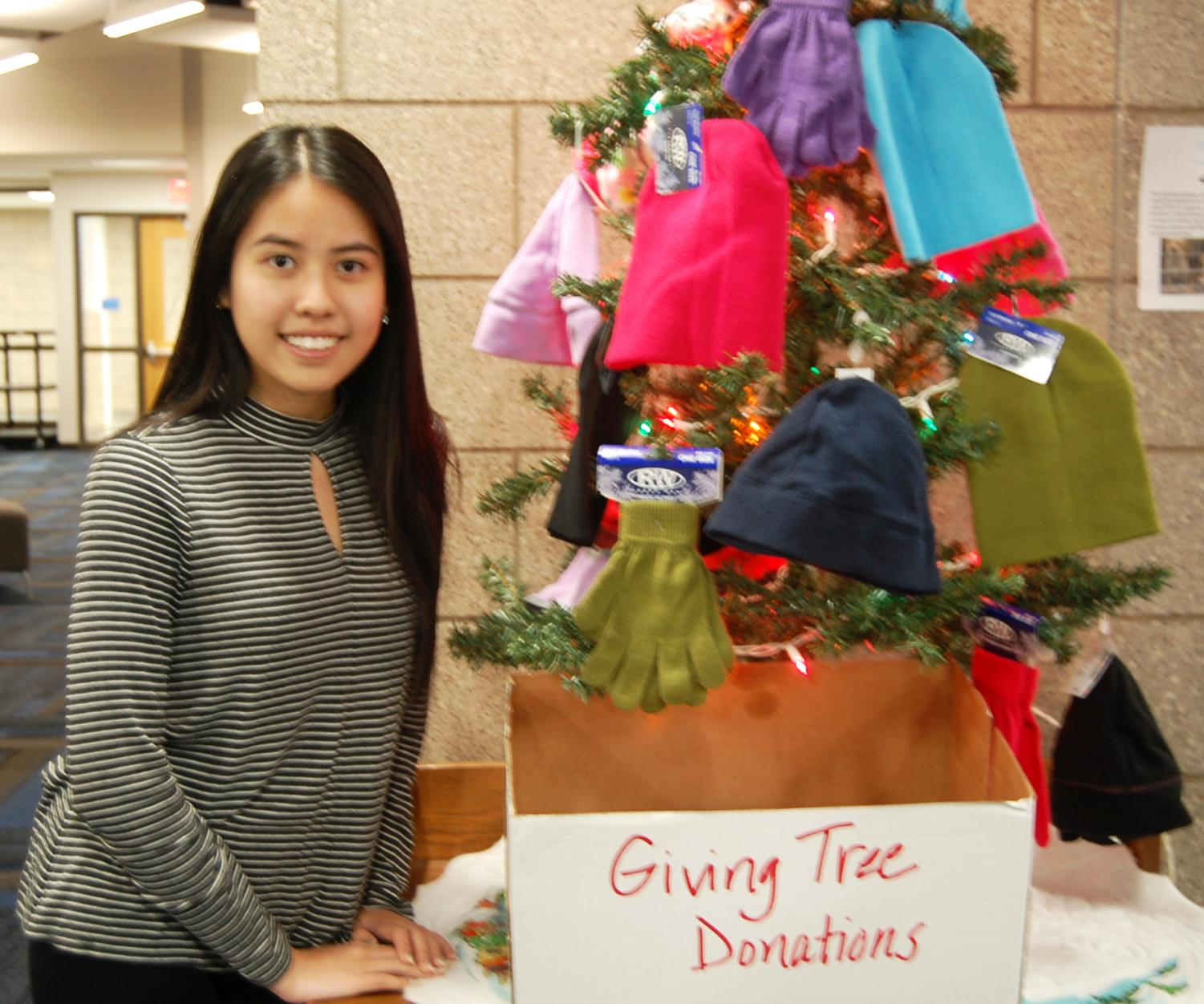 Senior Truc Nguyen poses by the Giving Tree on Dec. 20 during 5th hour in the Library Media Center.