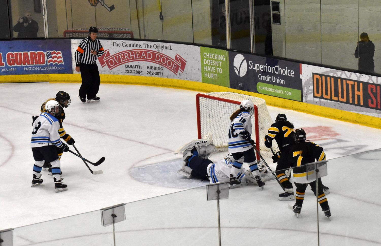 Spartan Goalie sophomore Katrina Casper (1) dives to stop the puck while freshman Callie Holmund (18) blocks the Marshall players.