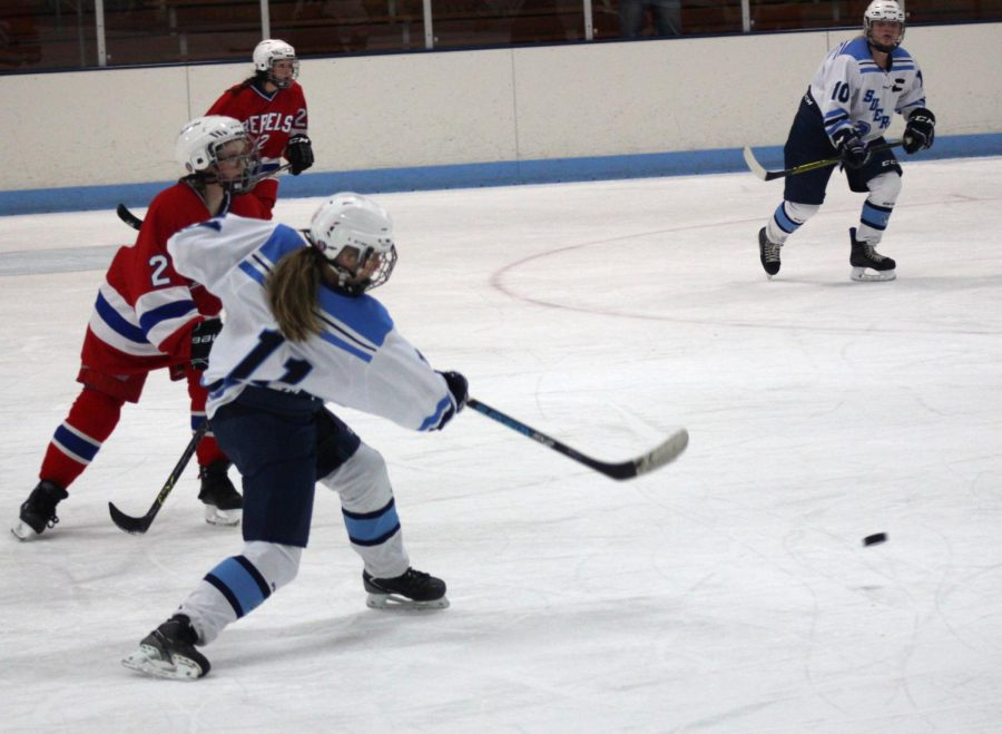 Freshman+Lily+Walrath+%2810%29+passes+the+puck+to+sophomore+Arika+Trentor+%2811%29+late+in+the+second+period+of+Tuesday%E2%80%99s+game+against+Moose+Lake+at+the+Superior+Ice+Arena.+The+Spartans+and+Rebels+tied+4-4.