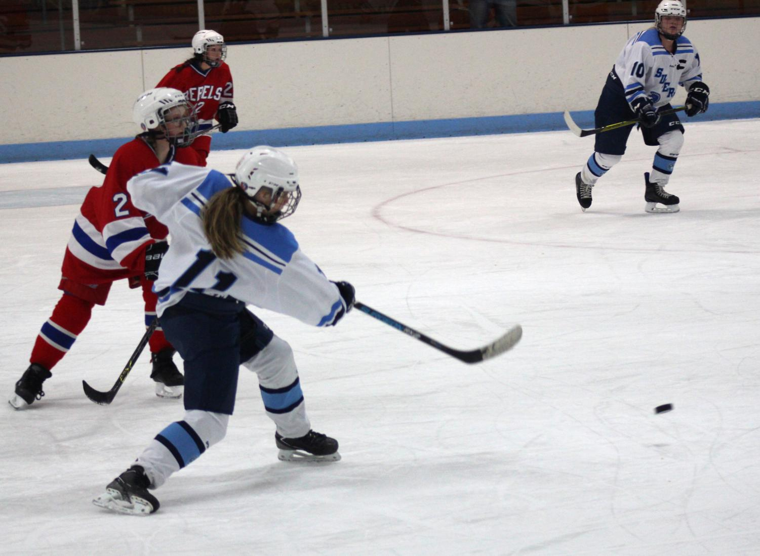 Freshman Lily Walrath (10) passes the puck to sophomore Arika Trentor (11) late in the second period of Tuesday's game against Moose Lake at the Superior Ice Arena. The Spartans and Rebels tied 4-4.
