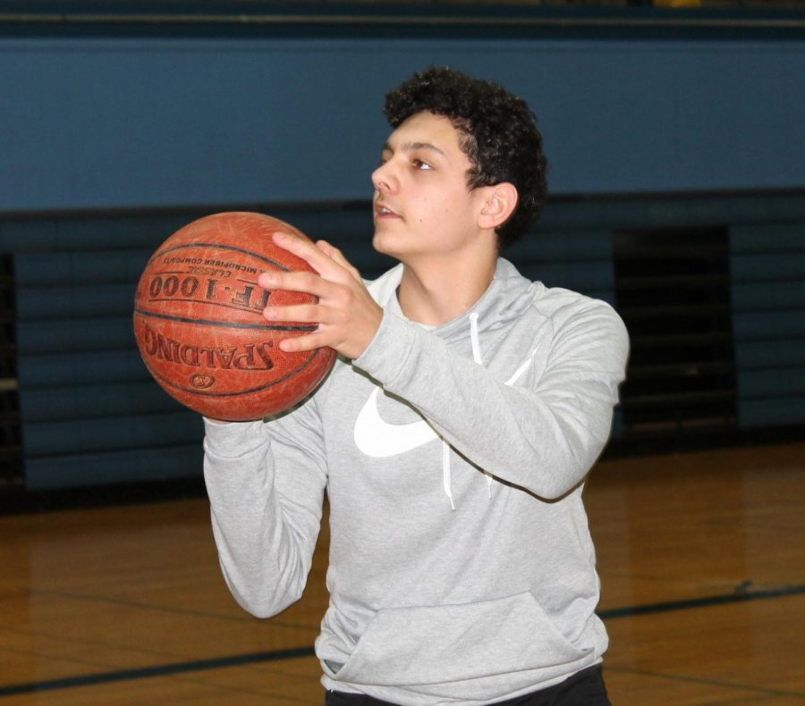 Sophomore+Malachi+Simiyu+practices+shooting+in+SHS+gym+on+Feb.+15.+He+measures+his+improvements+made+from+the+Fitnessgram+testing+in+his+gym+class.
