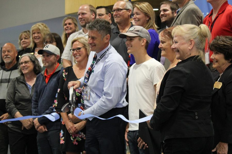 Principal Rick Flaherty cuts a ribbon last Wednesday evening in the Commons to formally honor the new high school that was built between 2017 and 2019. During the open house, the music department performed, leaders gave speeches and student council members gave tours.