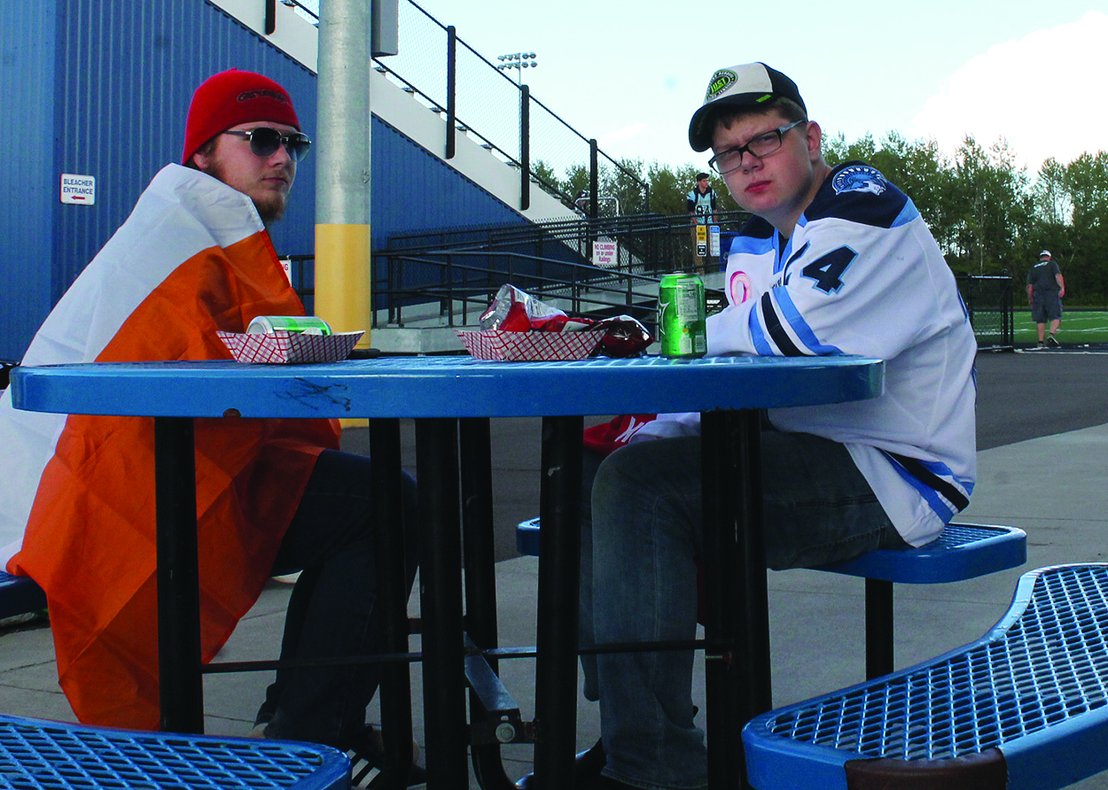 Sophomores Ethan Geegan (left) and Jack Curtis sit outside of the concession stand at the NBC Sports Complex at the DECA Tailgate event Friday, Sept. 6. DECA Tailgate raised over $3000 for the Superior Vocational Center.