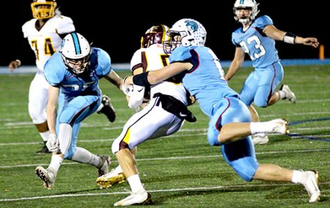 Senior Jarrett Gronski (6) takes down Menomonie's David Barthen (5) as senior Will Schorr (35) moves in on the play in the third quarter of a 14-13 victory at the NBC Spartan Sports Complex Oct 4. Spartan's senior Caden Stone (23) pursues the play.