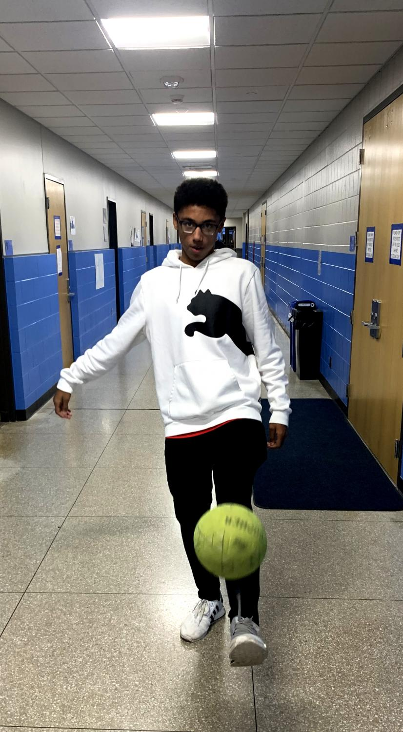 Freshman Darrell James kicks a soccer ball in the gym hallway Nov. 11. James says that he looks up to professional soccer player Lionel Messi.