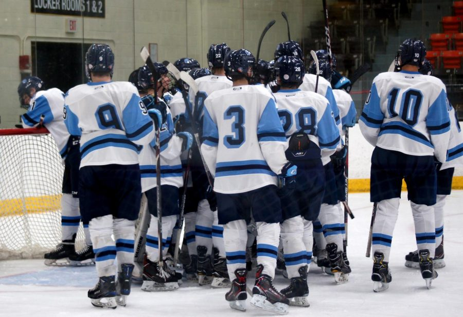 The Boys' Varsity Hockey team get together in a group hug after their 5-2 win against the Marshall Hilltoppers Dec. 3. This was a bounce back for the boys, losing both of their previous away games.