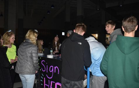 Student council members sign students up the raffle that took place at the dance on Feb. 5. The students would have a chance to win a pair of AirPods if they won.