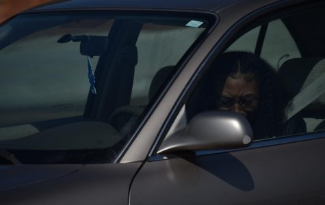 Senior Chassidy Wilkins tears up as she sees her teachers waving and cheering April 24. While staying in her vehicle and practicing social distancing, she was at the high school to  pick up her cap and gown for graduation.