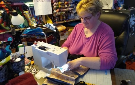 Walmart employee Nickola Boutelle  sews mask from home at her sewing table April 3.