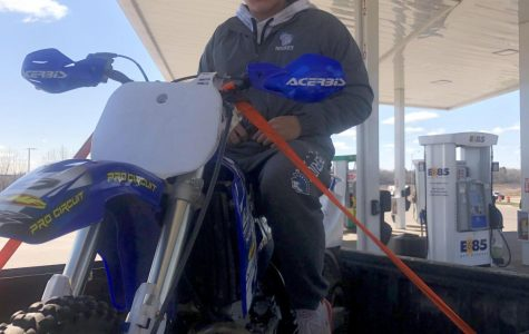 Sophomore Austin Ward sits on his Yamaha Yz250 in the back of a truck May 8. He needed to gas up the bike in city limits, but the law does not allow driving it in the city limits.