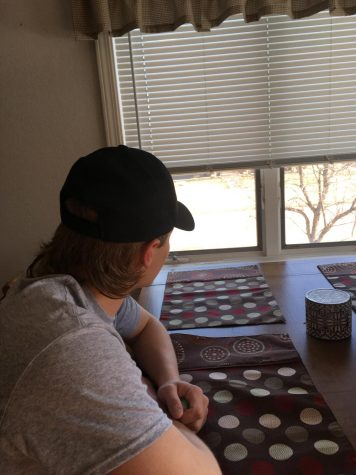 Senior athlete Brennan Morrissey looks outside at a sunny afternoon from his dining room table.