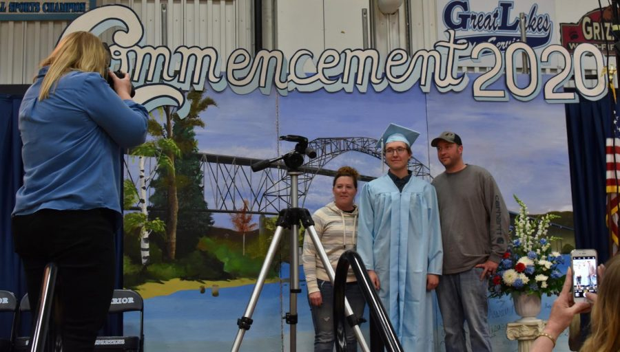 Tyler Moen, along with parents Alisha and Tyler Prendergast, pose for their family picture on the commencement stage for the class 2020.