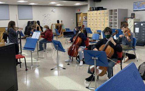 Orchestra Director Amy Eichers is conducting the Orchestra Students in class as well as the online students with her computer on Tuesday, September 29. Students in the class are wearing masks and social distancing.