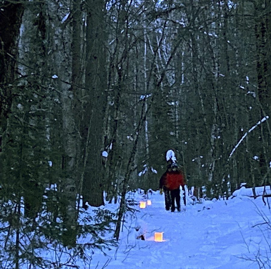 Gary Duzell and his son hike up a luminary-lit trail at the School Forest Feb. 20 after sunset.