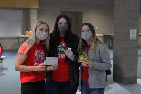 Senior Student Council President Faith Lach (right) is standing next to senior Mara McGillis (middle) and senior Sydnie DeMeyer (left) getting ready for the Movie Trivia Night Kahoot questions on Tuesday Mar. 29.