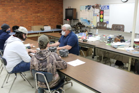 Bianchi is teaching a group of students a lesson on small gasoline powered motors.