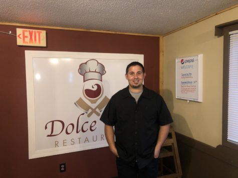 Chef and Owner Zudija Maksutoski stands on the right side of the Dolce Vita sign.