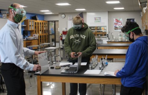 Tyler Ross explains an equation to an online student at the lab station in room 1150 while Trevor Bickford and Cameron Buck start the experiment May 4.