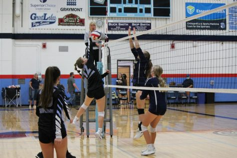 JV player Indigo Fish blocks the ball over the net at the game. Fish really helped the team out at their very first game.