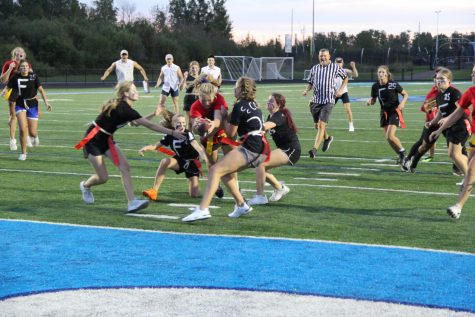 Junior Emma Raye dives over freshmen into the end zone Sept. 15. The Juniors ended up losing on a controversial coin flip while being tied 12-12